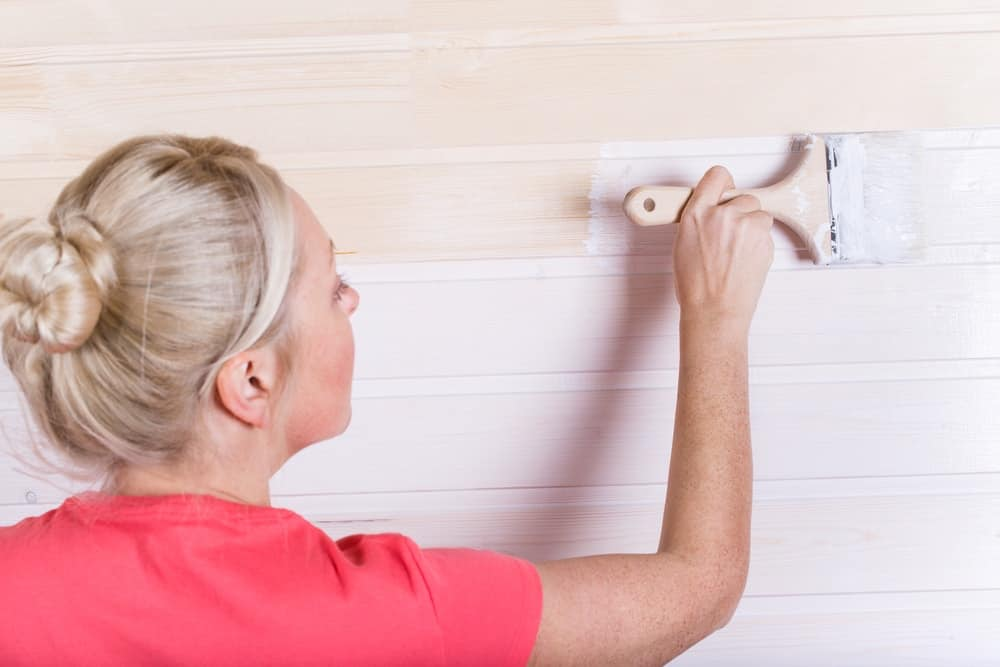 Woman painting wooden slot and key boards in white color.