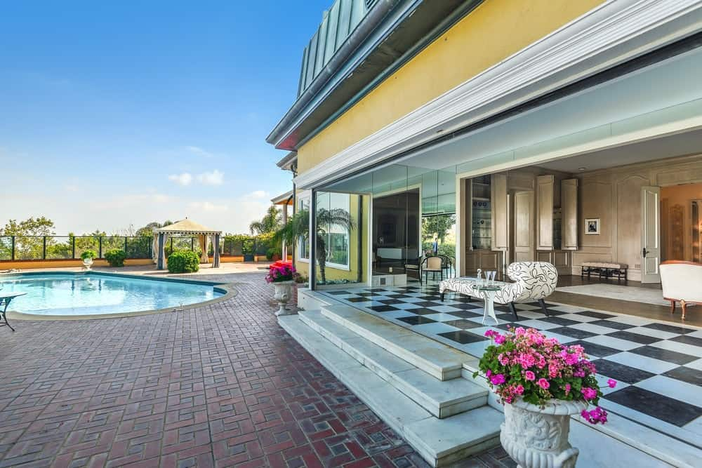 This view of the pool side boasts of the charming terracotta brick flooring leading from the concrete steps of the covered patio to the pool itself. Images courtesy of Toptenrealestatedeals.com.
