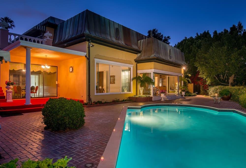 This night time view of the backyard pool shows that it has an ethereal glow from its own lighting augmented by the warm outdoor lights of the patio. Images courtesy of Toptenrealestatedeals.com.