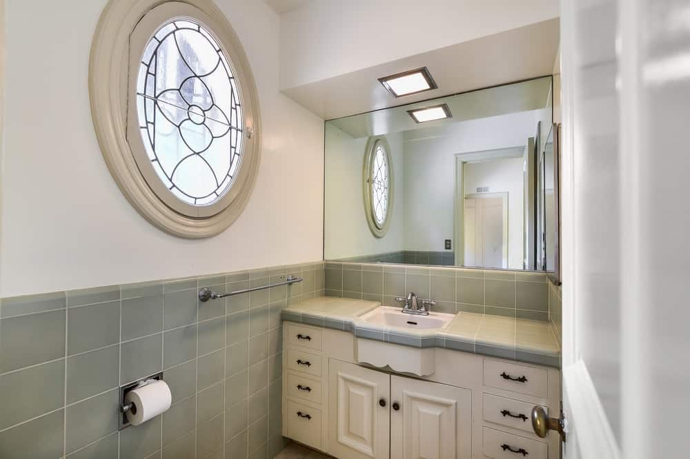 This bathroom has a charming circular window on the side of the vanity. The window has frosted glass that filters in the light and provides privacy. Images courtesy of Toptenrealestatedeals.com.