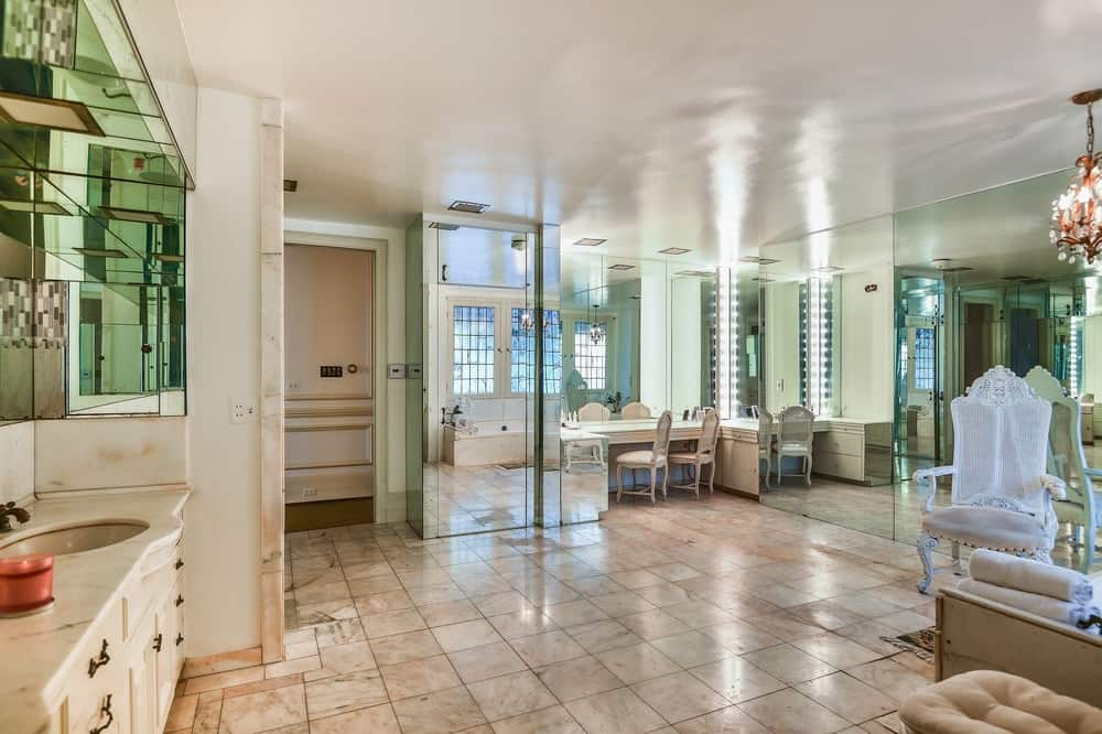 This other bathroom is complemented by the mirrored walls giving it an illusion of being bigger than it really is paired with beige flooring tiles to match the ceiling. Images courtesy of Toptenrealestatedeals.com.