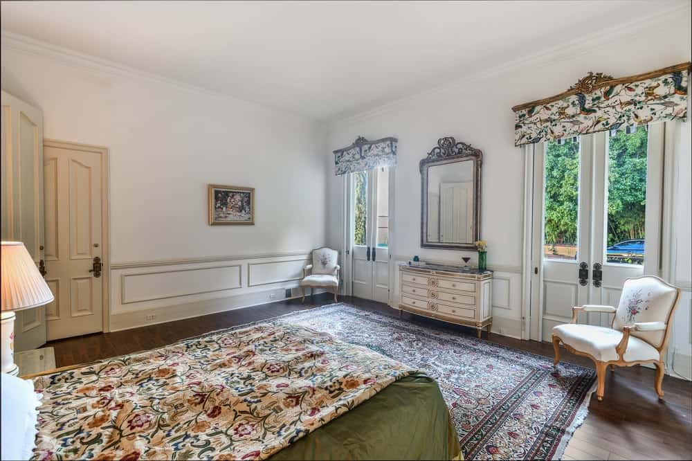 This bedroom has charming floral patterns to its bed sheet, area rug of the hardwood flooring and the shades of the two tall windows flanking the dresser and vanity. Images courtesy of Toptenrealestatedeals.com.