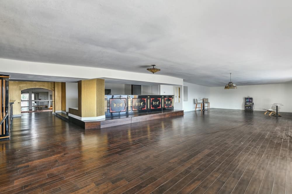 This large bonus room is perfect for large parties on its wide and spacious hardwood flooring that pairs well with the elegant bar on the side. Images courtesy of Toptenrealestatedeals.com.