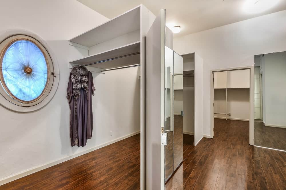 This spacious walk-in closet has various wooden structures built into the walls with shelves, racks and mirrors. Images courtesy of Toptenrealestatedeals.com.