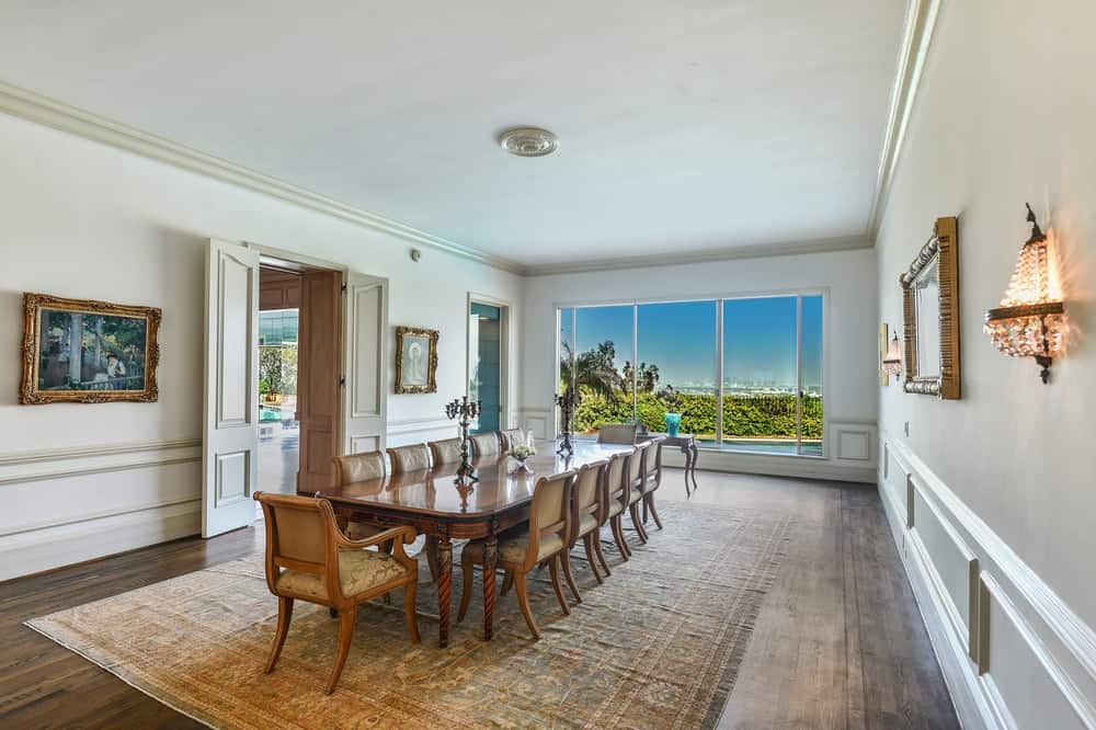 The formal dining room of the house has a long wooden dining table surrounded by wooden chairs that complement the bright walls and ceiling. Images courtesy of Toptenrealestatedeals.com.