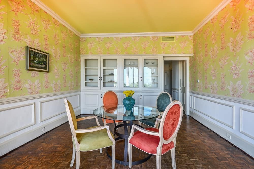 This lovely and intimate informal dining room has charming yellow walls complemented by white wooden wainscoting that makes the colorful cushioned chairs stand out as they surround the glass-top round table. Images courtesy of Toptenrealestatedeals.com.