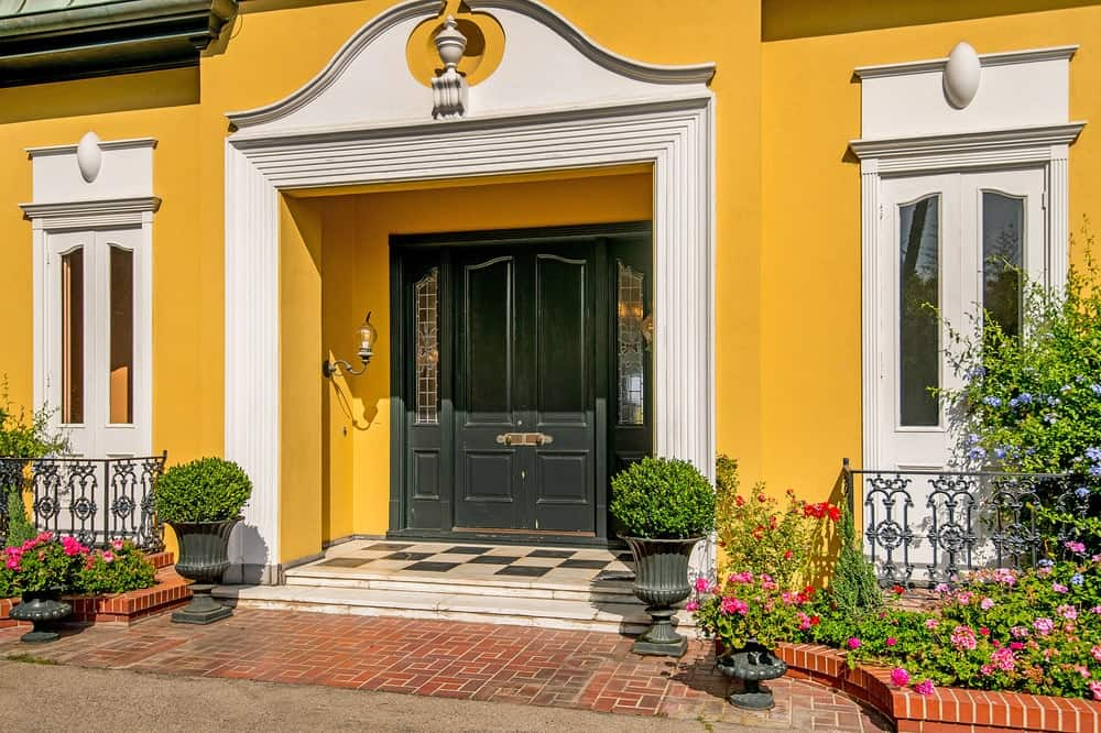 The main entry of the house has white elegant archway leading to a gorgeous black main door paired with a checkered white and black flooring. Images courtesy of Toptenrealestatedeals.com.