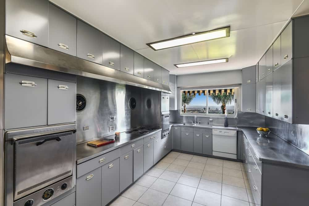 This modern U-shaped kitchen has lovely light gray cabinetry lining the walls that houses the cooking area, faucet area and stainless steel appliances. Images courtesy of Toptenrealestatedeals.com.