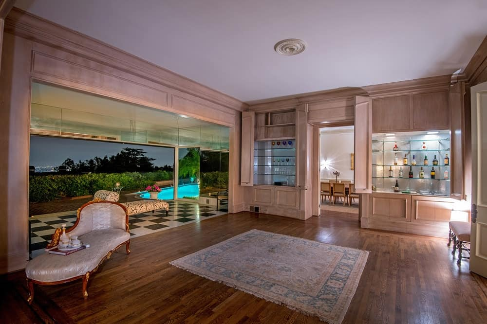 This spacious living room has a hardwood flooring complemented by a patterned area rug in the middle that matches with the wooden structure that houses the entryway to the dining room on the far side. Images courtesy of Toptenrealestatedeals.com.