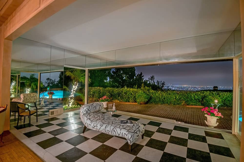 The covered patio has a wide white ceiling above the the gorgeous black and white checkered flooring that gives the area a unique character. Images courtesy of Toptenrealestatedeals.com.