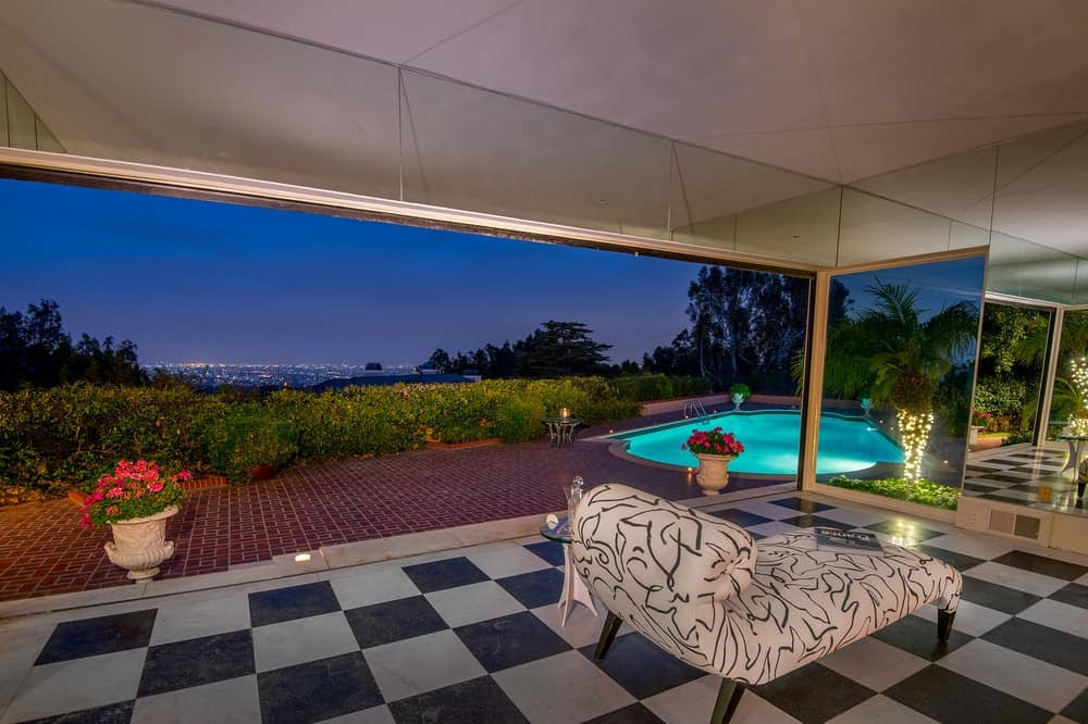 In the middle of the wide checkered flooring of the covered patio is a relaxing and comfortable cushioned day-bed perfect for lazy afternoons and evenings with a view of the city lights in the distance. Images courtesy of Toptenrealestatedeals.com.