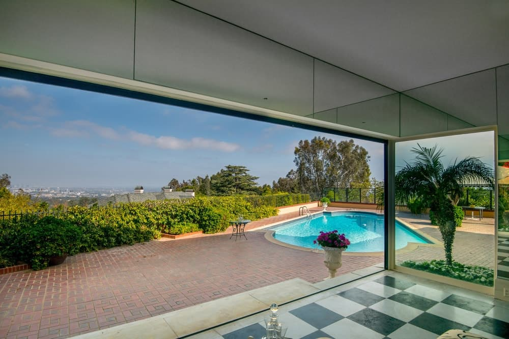 The covered patio with the checkered black and white flooring is just a few steps away from the backyard pool that is surrounded by terracotta walkways and lush shrubberies for a nice patio background. Images courtesy of Toptenrealestatedeals.com.