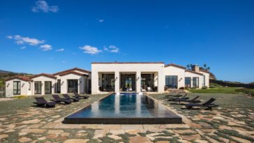 The gorgeous infinity pool of the backyard is a nice foreground for the back view of the house that has large open walls leading to this backyard poolside area with mosaic stone walkways and several lawn chairs for enjoying under the sun. Images courtesy of Toptenrealestatedeals.com.