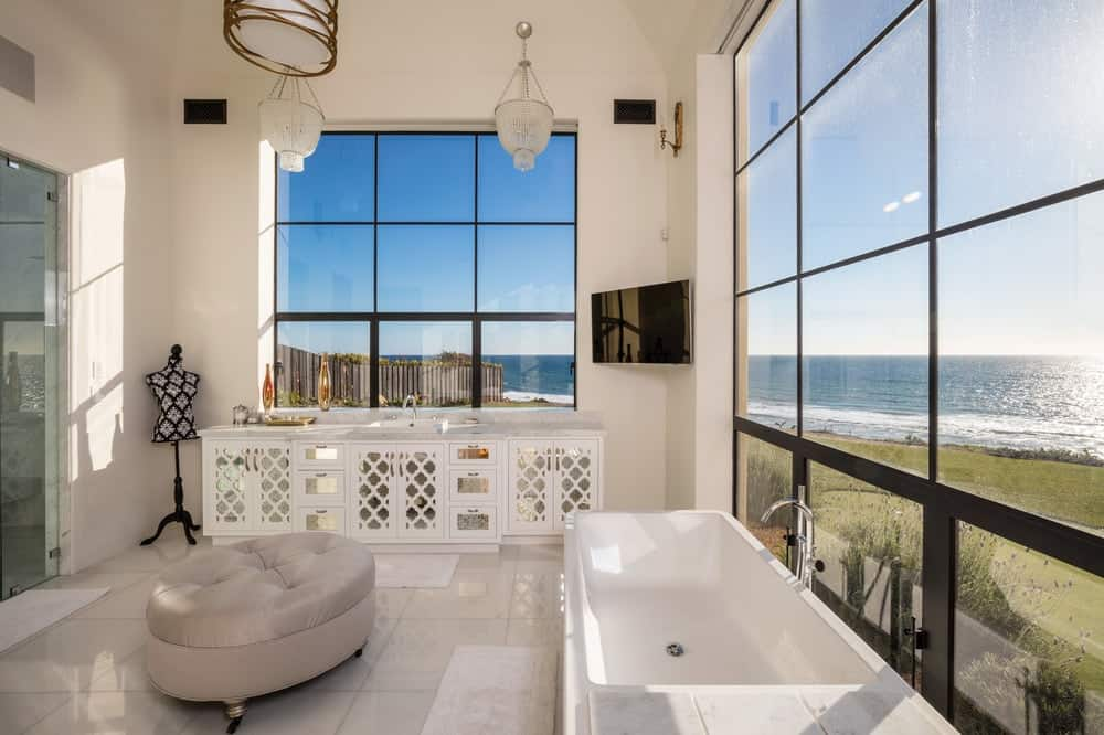 This gorgeous bathroom has a white vanity placed on the far side under the large window with a wall-mounted TV on the corner and a round cushioned ottoman in the middle of the beige-tiled flooring. Images courtesy of Toptenrealestatedeals.com.