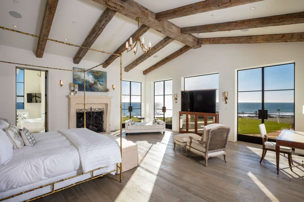 This is the primary bedroom with rustic exposed wooden beams on its beige cathedral ceiling that matches well with the hardwood flooring. The simple bed is warmed by the fireplace on the side with a beige mantle. Images courtesy of Toptenrealestatedeals.com.