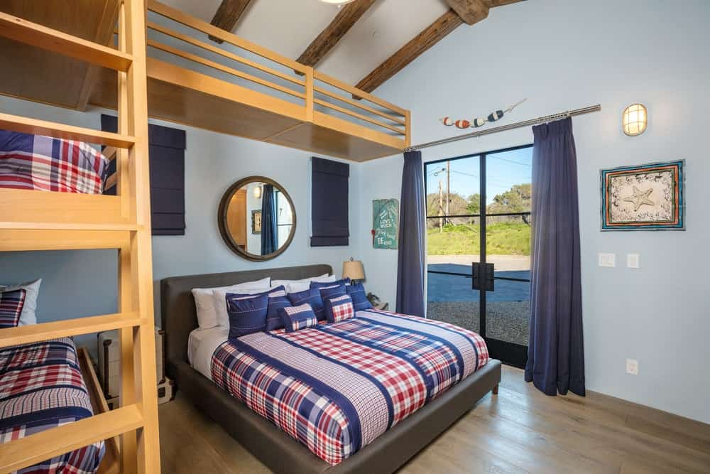 This is the bunk room that fits four beds with the help of a large wooden structure with a ladder on the side for the third tier bed near the cathedral ceiling with exposed beams. Images courtesy of Toptenrealestatedeals.com.
