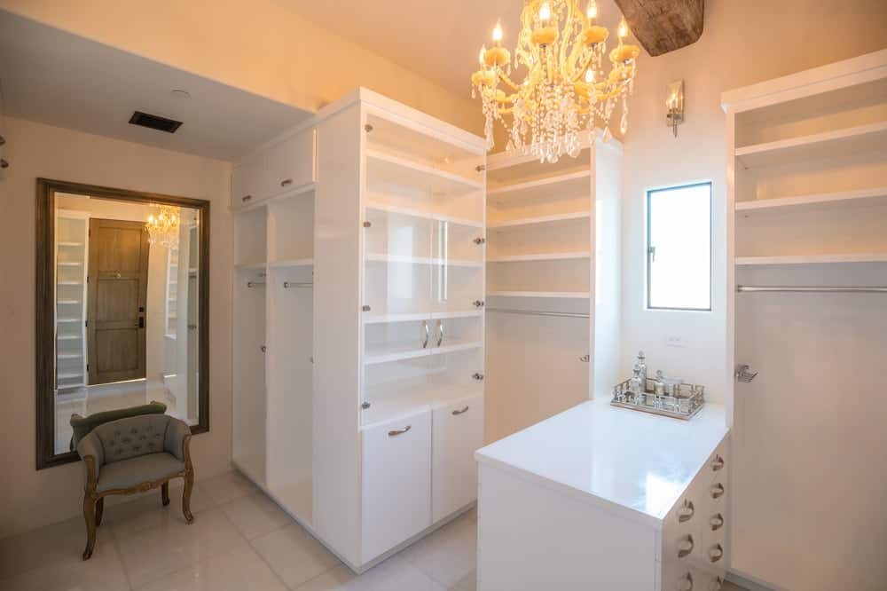 The walk-in closet of the house has sleek white cabinetry that is complemented by the beige walls and warm yellow light of the chandelier hanging over the white countertop. Images courtesy of Toptenrealestatedeals.com.