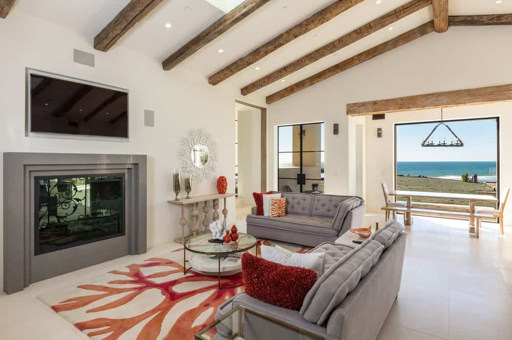 This is the cozy living room beside the kitchen with a modern fireplace across from the gray sofas and glass-top coffee table. Images courtesy of Toptenrealestatedeals.com.