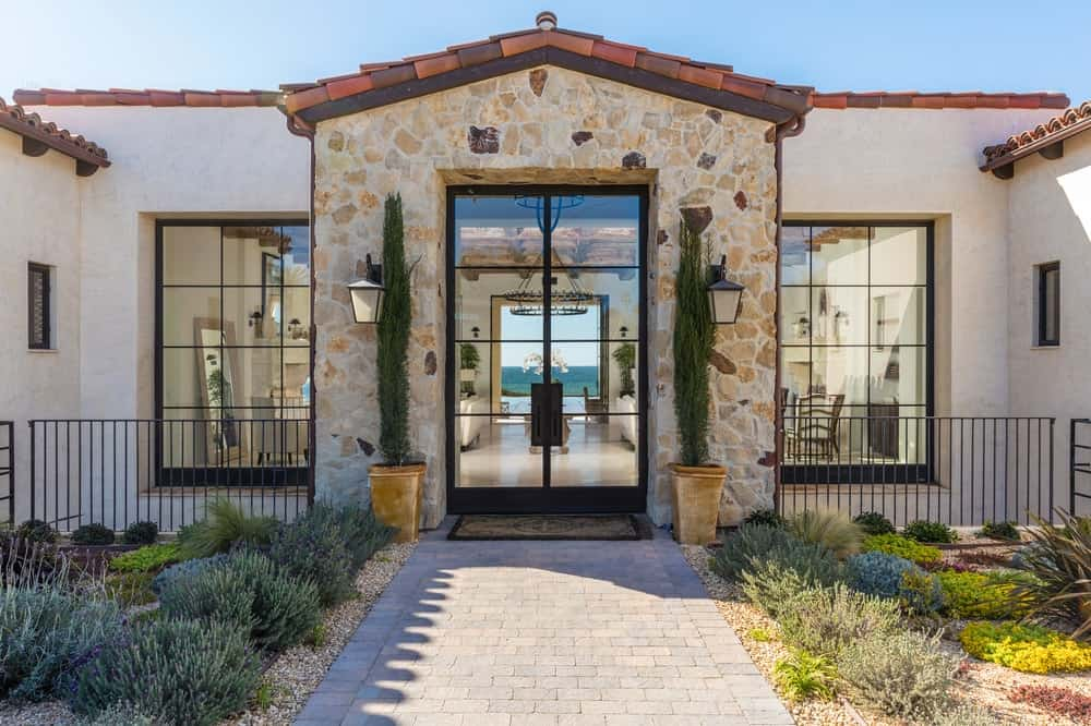This is the main entrance of the house with a stone brick walkway flanked by shrubs leading to a large glass door flanked with potted plants and large windows. Images courtesy of Toptenrealestatedeals.com.