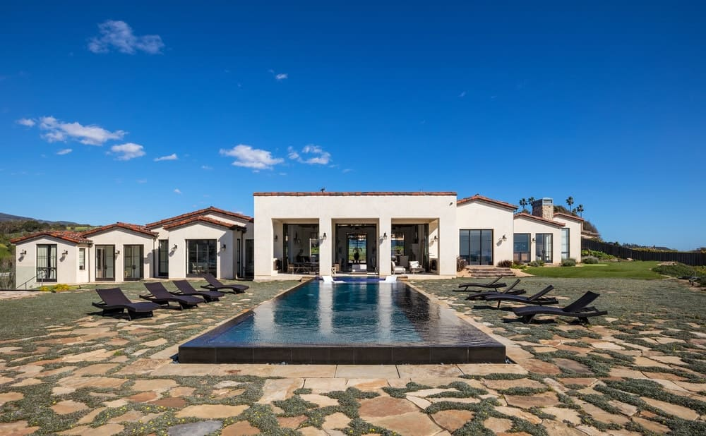 Outside view of the house showcasing its stunning custom swimming pool with black sitting lounges on both sides.