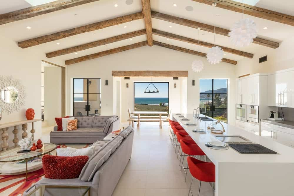 This great room houses the kitchen and a small living room under its large cathedral ceiling with exposed wooden beams and large openings at the far end. Images courtesy of Toptenrealestatedeals.com.