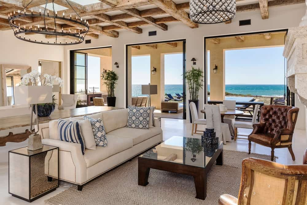 A different angle of this living room shows that it is bathed in natural lighting from the large open walls that complements the beige sofa and its wooden coffee table. On the far side, you can also see an informal dining area with a small round table. Images courtesy of Toptenrealestatedeals.com.