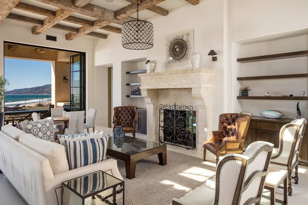 This living room has a large fireplace with a beige mantle that blends well with the walls topped with wall-mounted artwork and a round pendant light. Images courtesy of Toptenrealestatedeals.com.