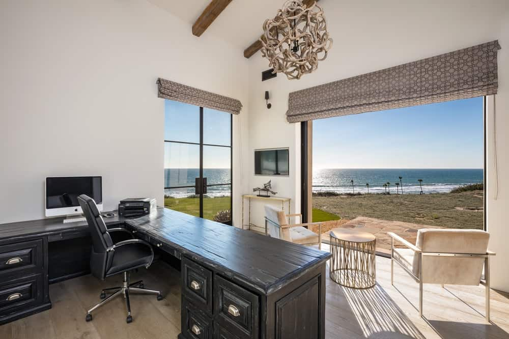 This beautiful office has a bright and airy look that is afforded by the large open wall and large window that brings the beautiful outdoors into the beige walls of the office that is contrasted by the dark wooden desk. Images courtesy of Toptenrealestatedeals.com.