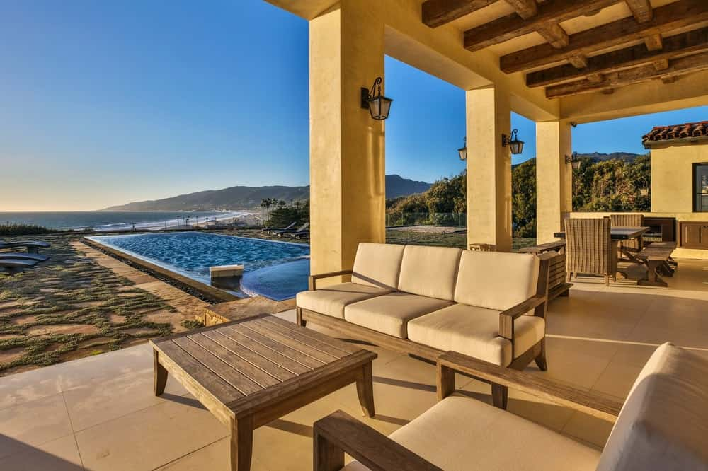 This is the covered patio right next to the pool. It has gorgeous tall pillars that support the tall ceiling complemented by exposed wooden beams. The cushioned sofa is paired with a simple and charming wooden coffee table. Images courtesy of Toptenrealestatedeals.com.