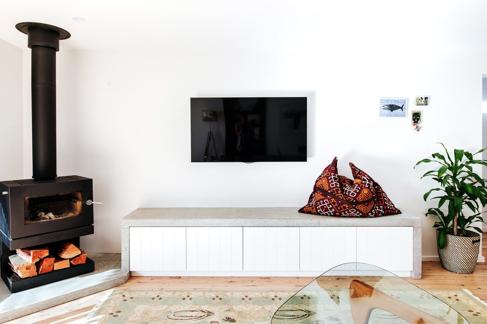 On the side of the fireplace is a built-in concrete structure that serves as an entertainment cabinet underneath the wall-mounted TV with built-in drawers.