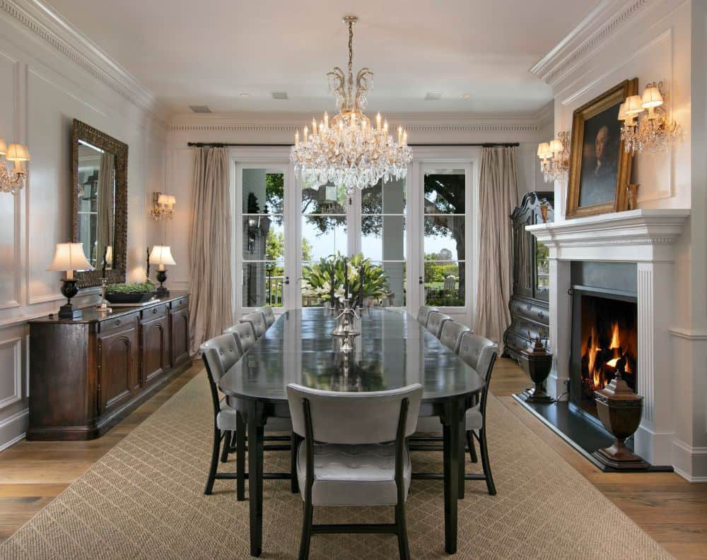 This elegant formal dining room has a large and sleek black dining table topped by a majestic crystal chandelier hanging from the white ceiling that matches the white mantle of the fireplace on the side.
