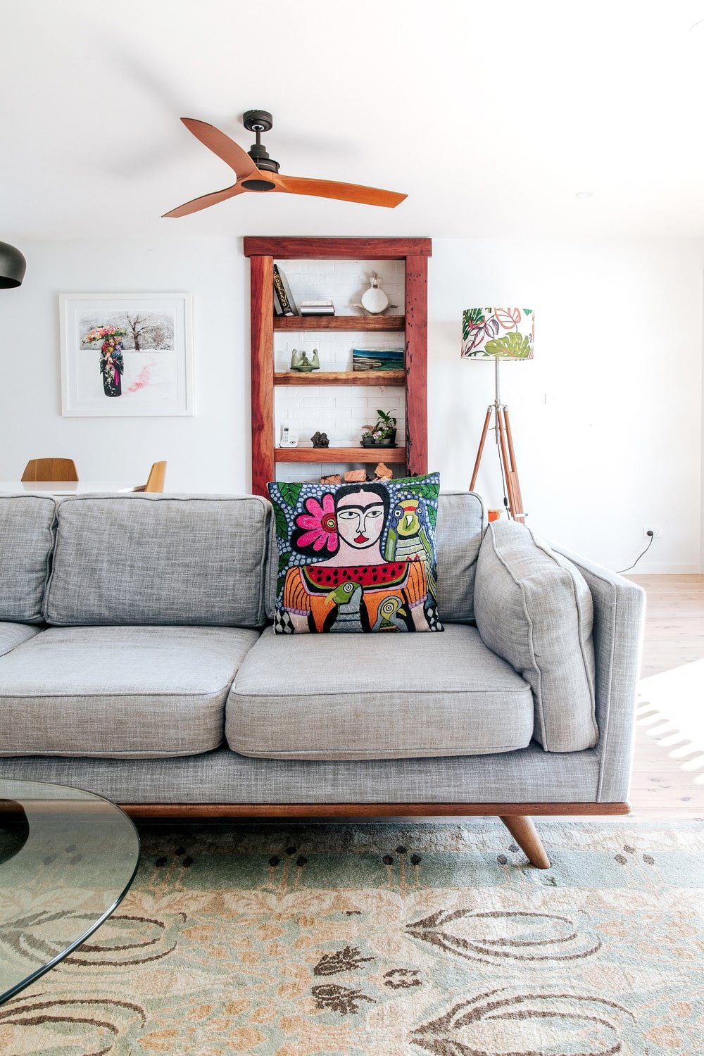 A closer look at the gray sofa reveals that it also has wooden legs like the armchair. This also matches with the built-in wooden shelf on the far wall behind the sofa.