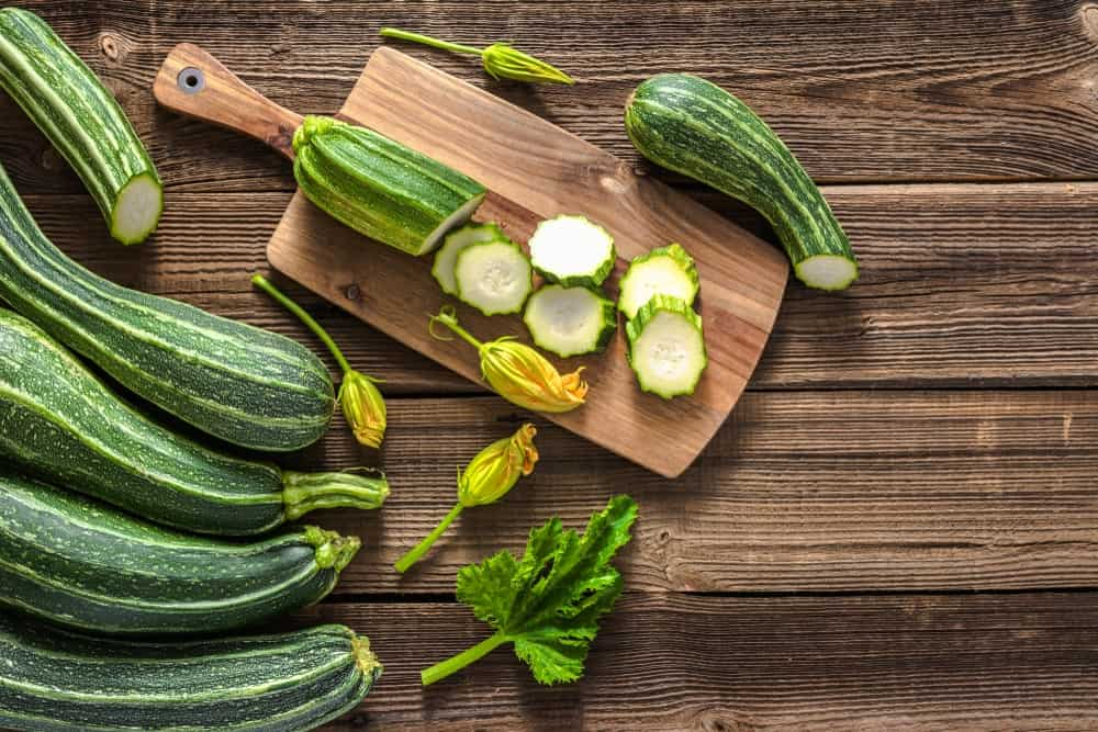 A bunch of zucchinis on a wooden surface.