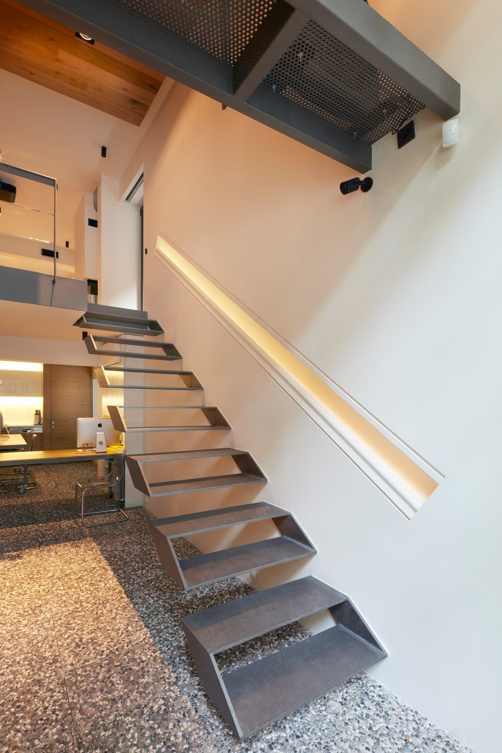 This is a closer look at the gray modern floating staircase with a handle embedded into the wall beside it.