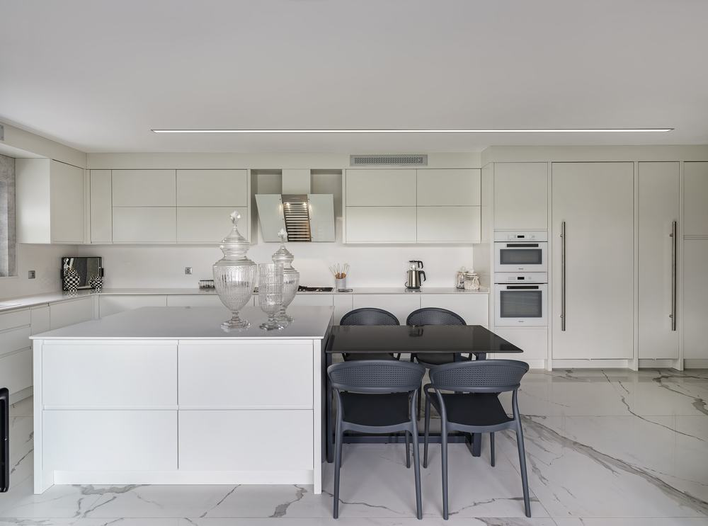 This lovely modern white kitchen has white cabinetry and white countertops to match the white walls and white ceiling. These are then contrasted by the built-in black dining table to the kitchen island paired with black chairs.