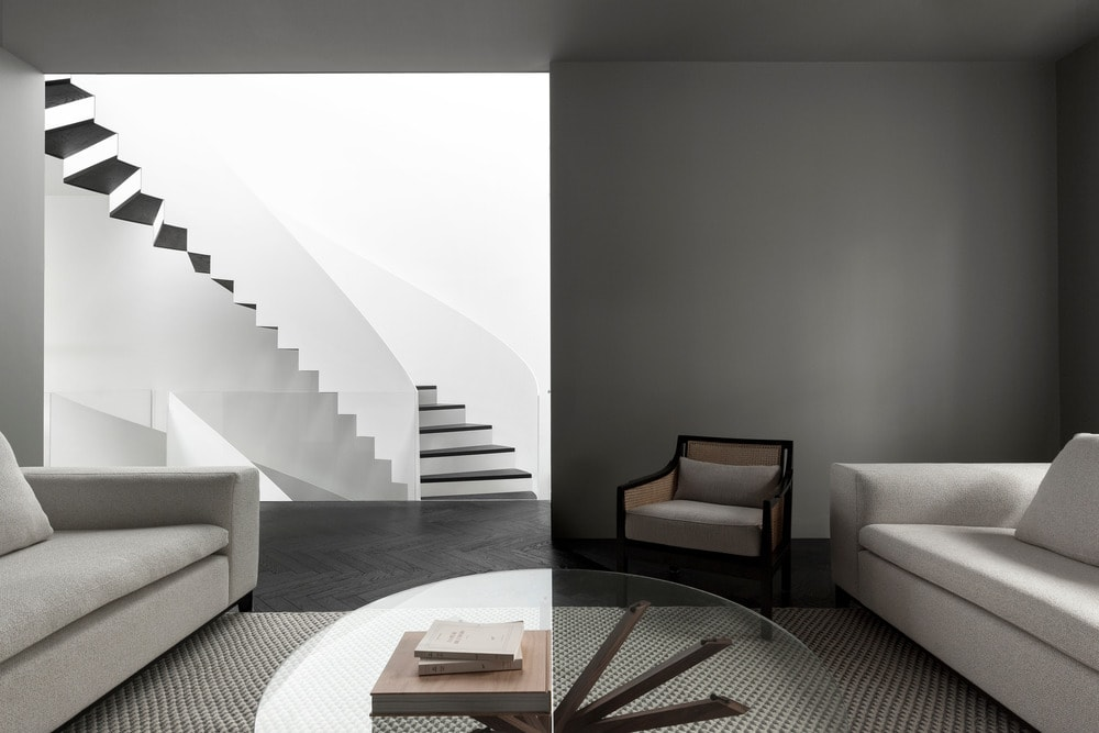This living room can be seen from the white spiral staircase with black accents to follow the aesthetic.