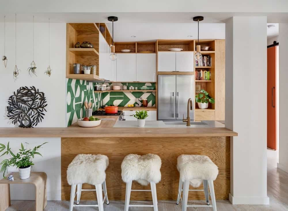 This view of the kitchen showcases the L-shaped peninsula with a wooden breakfast bar paired with white stools to match the white walls. This peninsula is attached to a thick white column that connects the floor to the white ceiling.