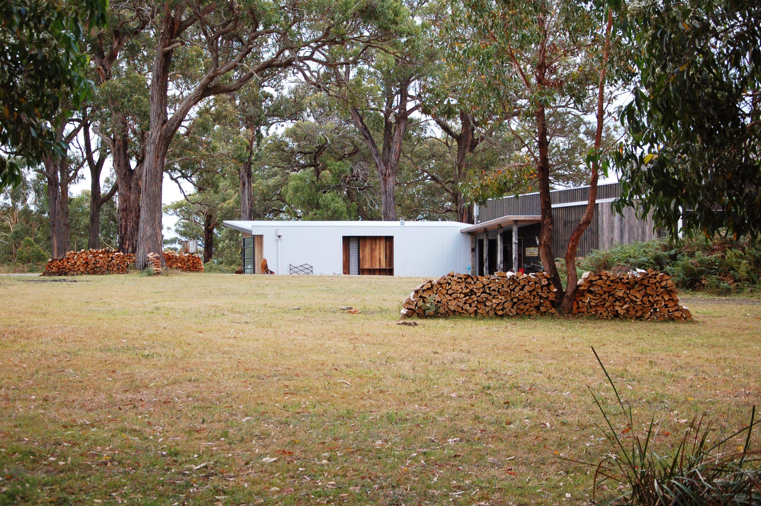 The front of the house has a large lawn of grass with shrubs and tall trees that give a nice background for the white exterior walls of the house. Here you can also see the piles of firewood stored beside the trees.