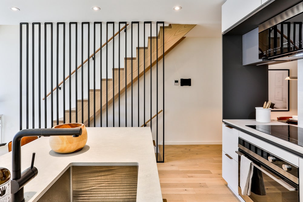 This is the view from the kitchen showing the staircase beside it. It has a large panel of thin iron bars that works for aesthetic and safety purposes. This gives accent to the wooden tone of the stairs that pair well with the hardwood flooring.