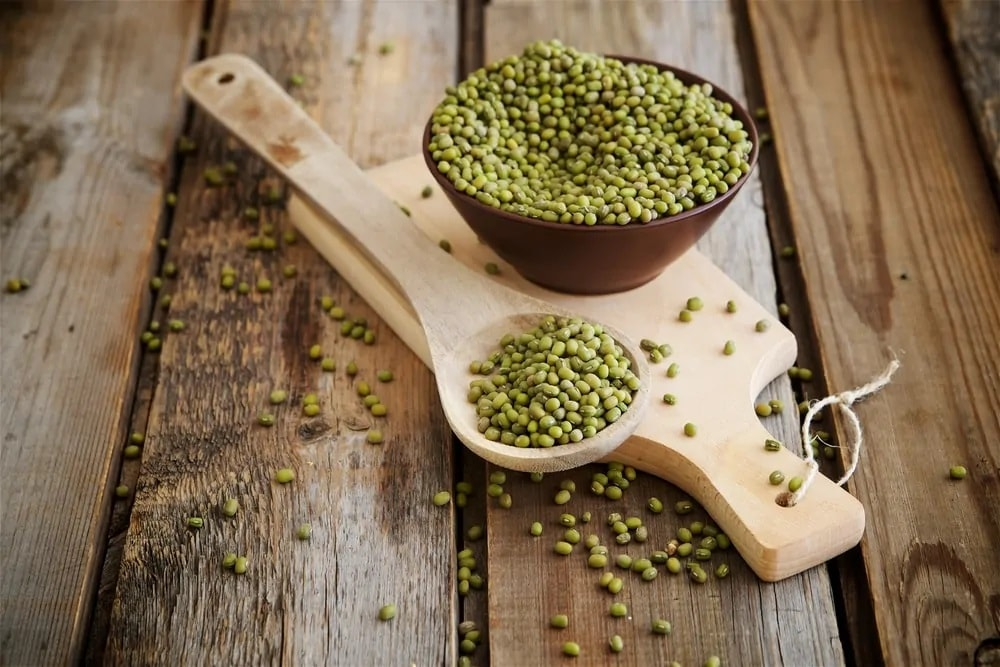 A bunch of mung beans in a brown bowl with a wooden spoon and a wooden chopping board.