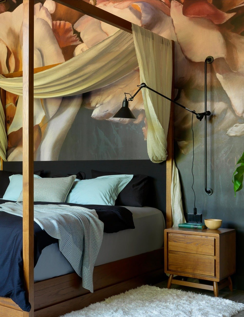 This bed is flanked by charming wooden bedside drawers that match perfectly with the tone of the bed frame. Here you can also see that the bed has a black headboard that blends well with the mural behind it.