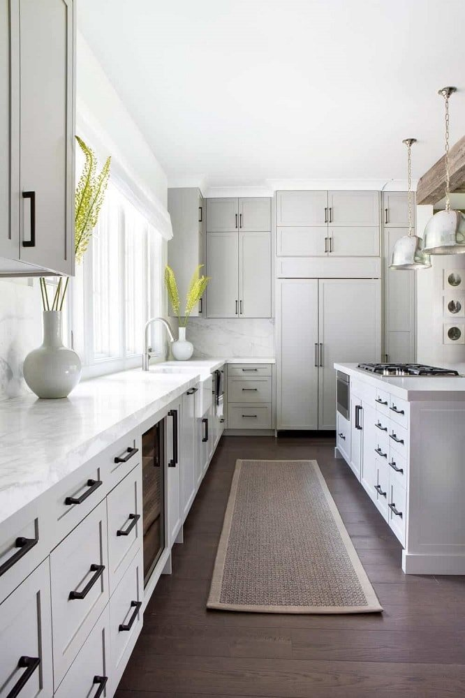 The black handles and fixtures of this long and narrow kitchen stands out against the brilliant white cabinetry that also contrasts the dark hardwood flooring. These are further brightened by the windows above the faucet area.