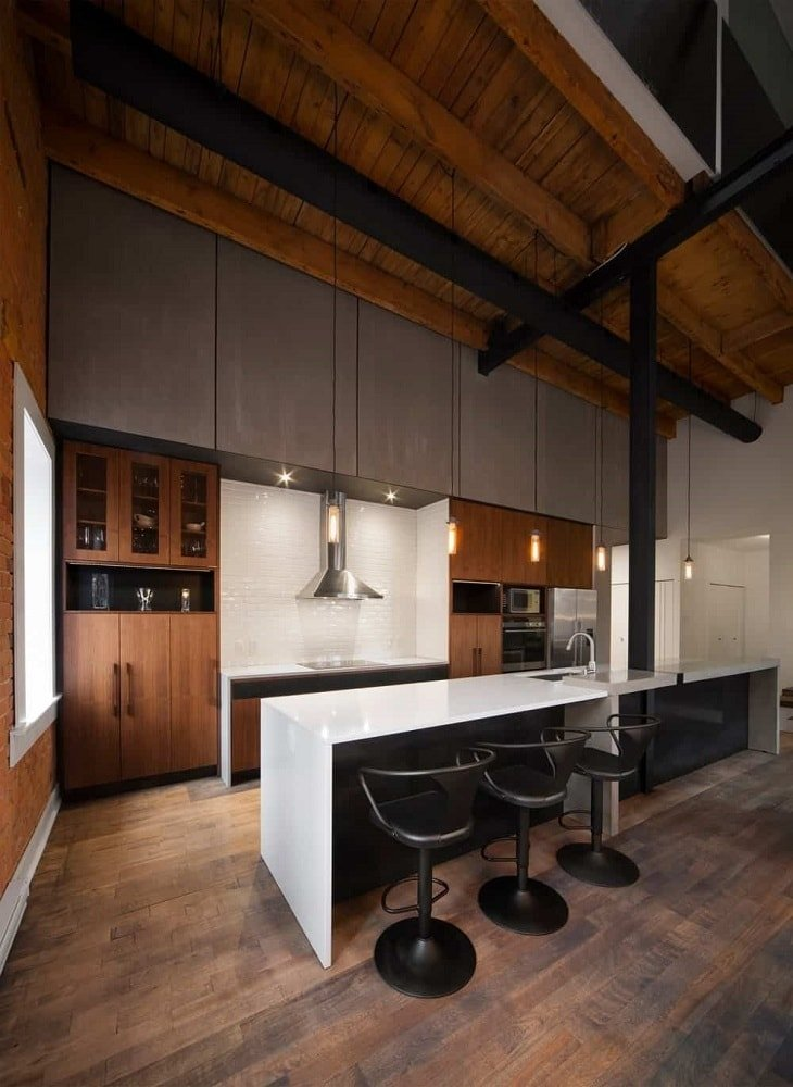 This view of the galley-style kitchen shows the large kitchen island with a breakfast bar attached to the black beams of the arched ceiling through a black column right in the middle. These elements are complemented by the lovely dark hardwood flooring.
