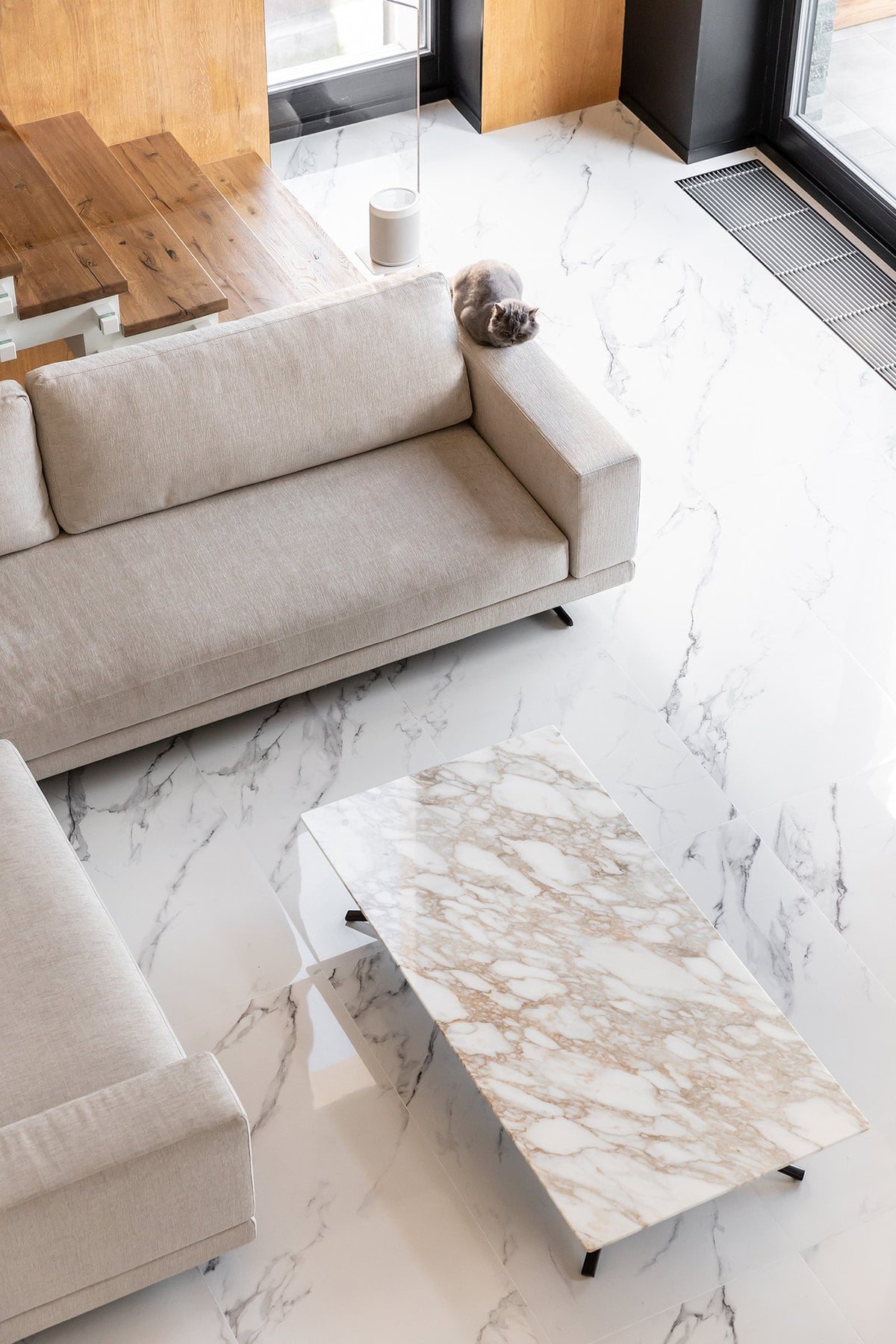 This is a top view of the L-shaped sectional sofa that stands out against the white marble flooring and pairs well with the coffee table.