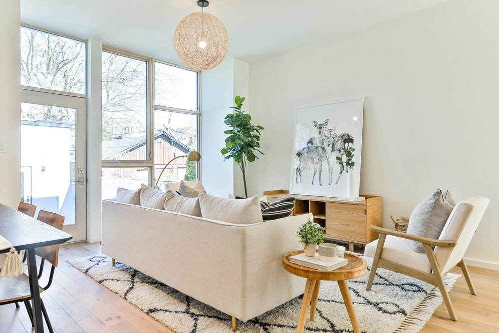 This is a closer look at the living room area with a beige sofa, a small round wooden side table and an armchair that pairs well with the large patterned area rug.