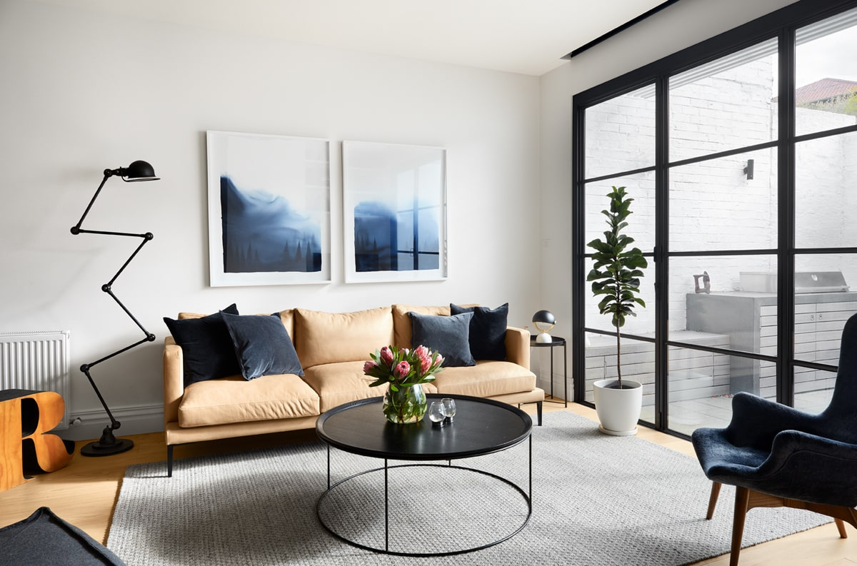 This is the beautiful and homey living room with a large beige sofa paired with a round black coffee table that stands out against the light gray area rug.