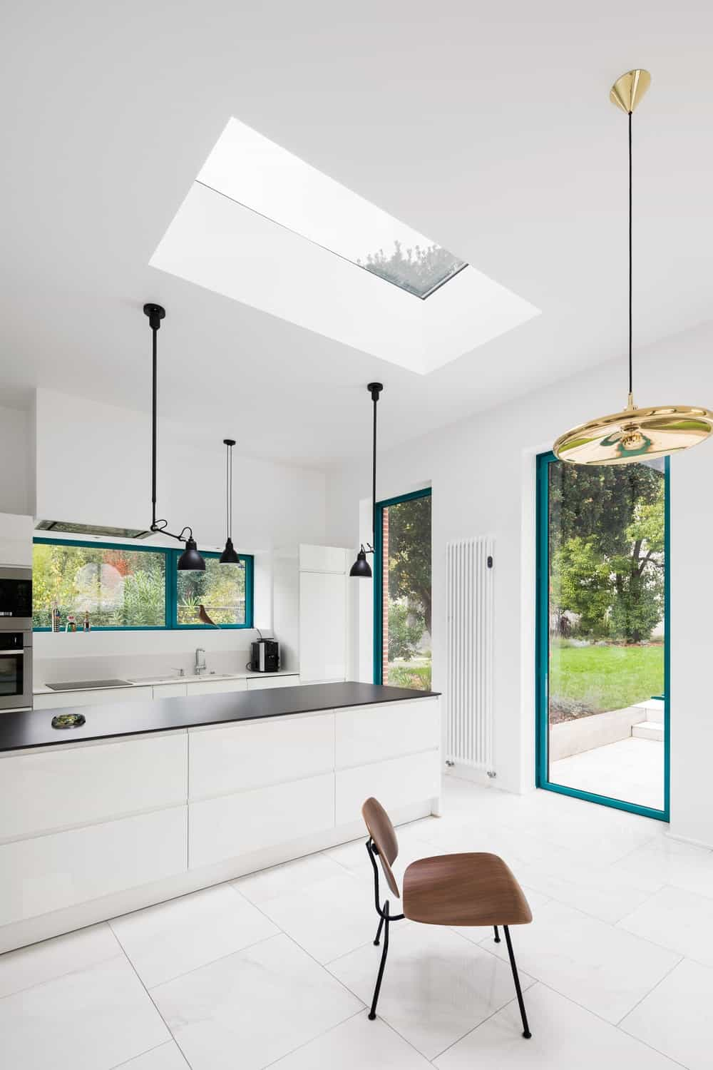 This is a simple and brilliant modern kitchen with a long and narrow design. It has a long white kitchen island contrasted by the black matte countertop toppe diwth a bright ceiling that has a skylight.