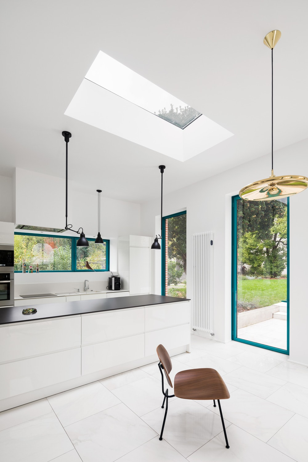 This angle shows more of the brilliant skylight of the white ceiling. This brings an abundance of natural lighting to the kitchen island that has a contrasting black countertop.