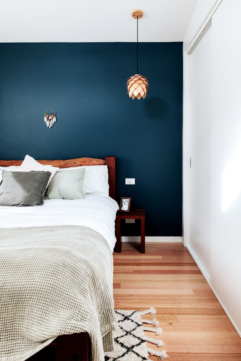 The primary bedroom has a large bed with a wooden headboard that matches with the small bedside table. These are complemented by the matte navy blue wall that makes the decorative pendant light stand out.