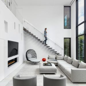This modern living room has a large glass wall on one side and a large white wall on the other that houses the modern fireplace and the TV. These pair well with the light gray sectional sofa and its cushioned coffee table.